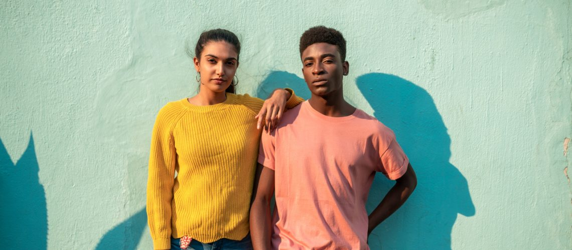 Portrait of Young couple. They are looking at camera while leaning on light blue wall.